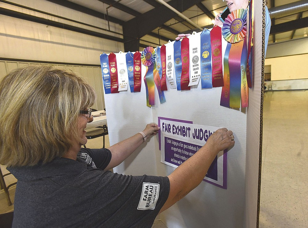 RIBBONS READY FOR FAIR Janice Shofner, a 4-H agent with the University of Arkansas Extension Service, puts together a display of ribbons on Saturday July 24 2021 at the Benton County Fairgrounds auditorium west of Bentonville. Extension agents, Benton County Fair officials and volunteers were on hand during an open house to answer questions and hand out information for people wishing to enter livestock, food, crafts or other goods in the 117th annual Benton County Fair set for Sept. 28-Oct. 2. People could also find out about dozens of free classes for youths and adults to help them be successful exhibitors. The fair office will open at the fairgrounds Sept. 22-23 for participants to pick up exhibit tags and fair passes. A pre-fair horse show takes place at 9 a.m. Sept. 25. Sept. 28, opening day, is military, first responder and health care wrokers appreciation day. Go to nwaonline.com/210725Daily/ to see more photos. (NWA Democrat-Gazette/Flip Putthoff)
