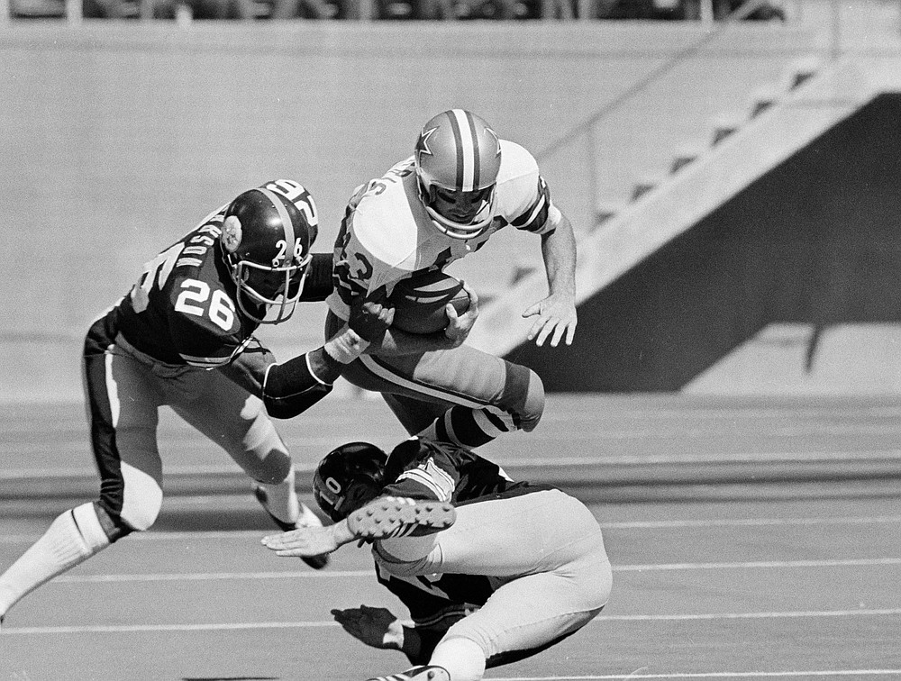 File-This Oct. 8, 1972, file photo shows Dallas Cowboys safety Cliff Harris (43) making a 45-yard return on a second quarter punt Oct. 8, 1972 in Irving, Texas before being brought down by Steelers' Preston Pearson (26) and Roy Gerela (10). Harris and receiver Drew Pearson, who also will be inducted this year as part of the class of 2021, are the first undrafted Cowboys among their 15 players in the Hall of Fame.(AP Photo/File)