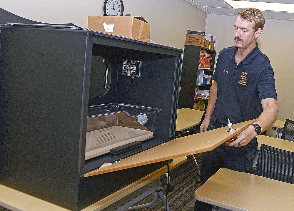 Fort Smith firefighter Charles Little opens the interior door of a Safe Haven Baby Box that will be installed in an exterior wall at Fort Smith Fire Station 11, 8900 Massard Road. The box is climate controlled and has a silent alarm transmitted to the dispatch center when the exterior door is opened.(Special to NWA Democrat Gazette/Brian Sanderford)