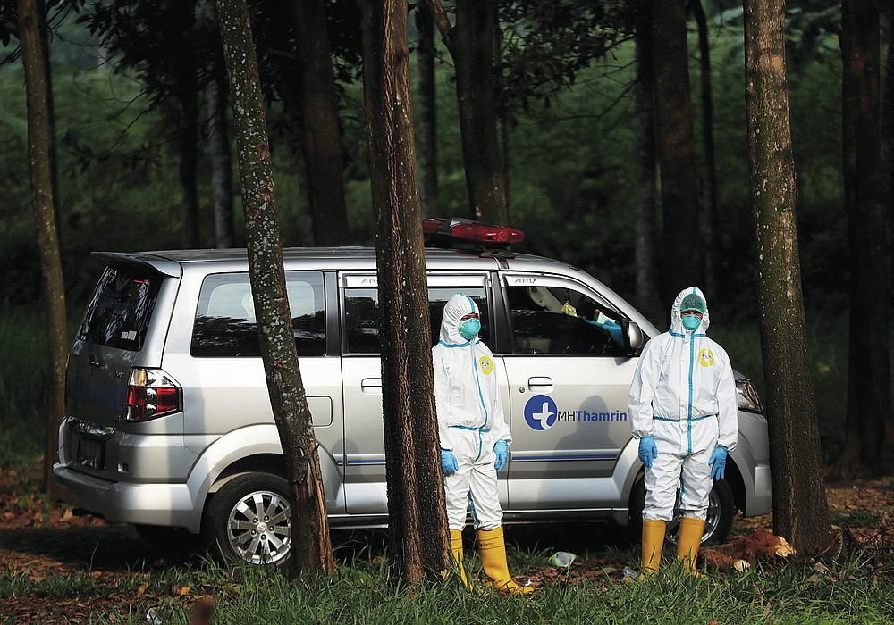 Workers in protective suits stand near an ambulance carrying the body of a COVID-19 victim as they wait for a grave to be prepared, at Cipenjo cemetery in Bogor, West Java, Indonesia on July 14, 2021. With the numbers of death increasing from the latest virus surge in Indonesia which has crippled the healthcare system in Java and Bali, relatives and residents decided to volunteer to dig graves using their own hoes and shovels to help exhausting gravediggers. (AP Photo/Achmad Ibrahim)