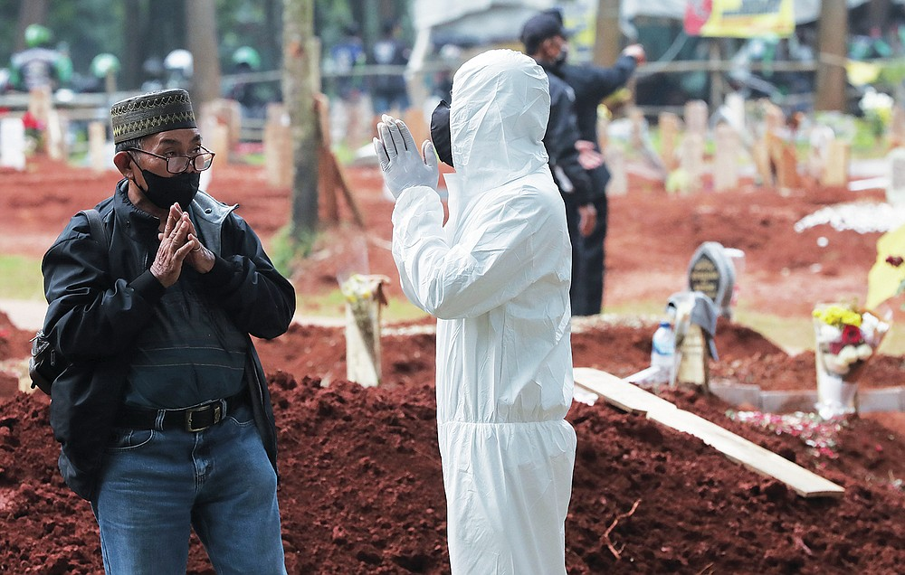 A man gestures as he speaks to a family in protective suit after a burial of a relative at Cipenjo cemetery in Bogor, West Java, Indonesia on July 14, 2021. With the numbers of death increasing from the latest virus surge in Indonesia which has crippled the healthcare system in Java and Bali, relatives and residents decided to volunteer to dig graves using their own hoes and shovels to help exhausting gravediggers. (AP Photo/Achmad Ibrahim)
