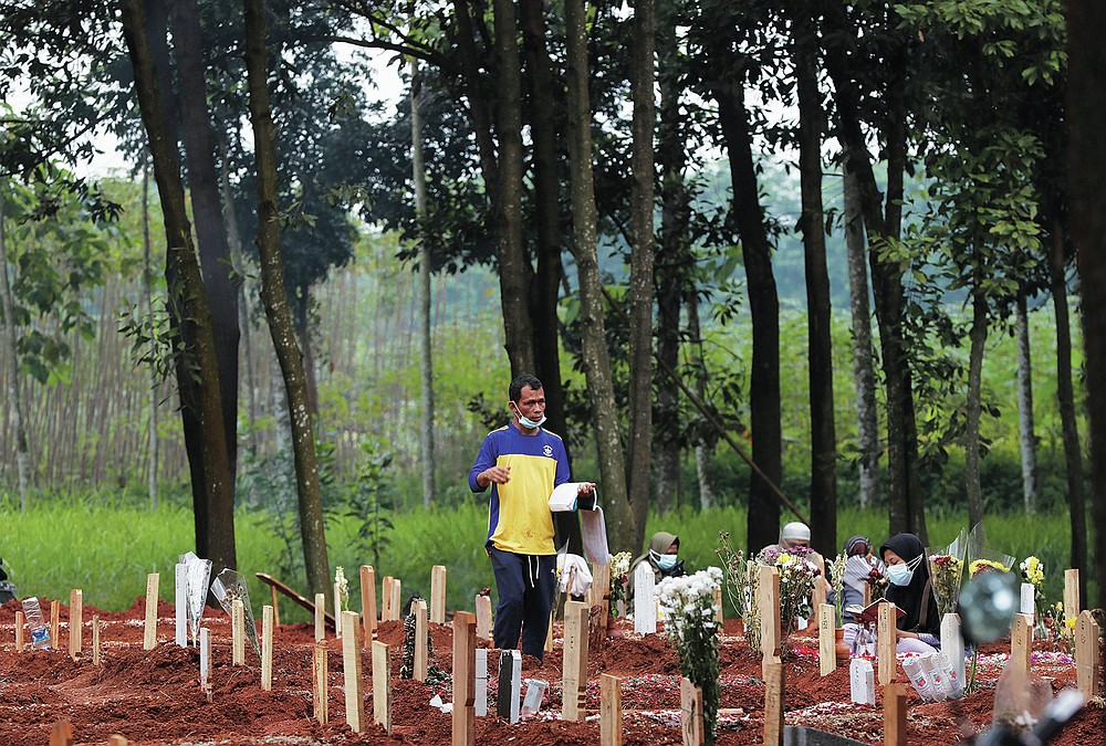 Jaidi, a cemetery worker, walks among graves of COVID-19 victims at Cipenjo cemetery in Bogor, West Java, Indonesia on July 14, 2021. With the numbers of death increasing from the latest virus surge in Indonesia which has crippled the healthcare system in Java and Bali, relatives and residents decided to volunteer to dig graves using their own hoes and shovels to help exhausting gravediggers. (AP Photo/Achmad Ibrahim)
