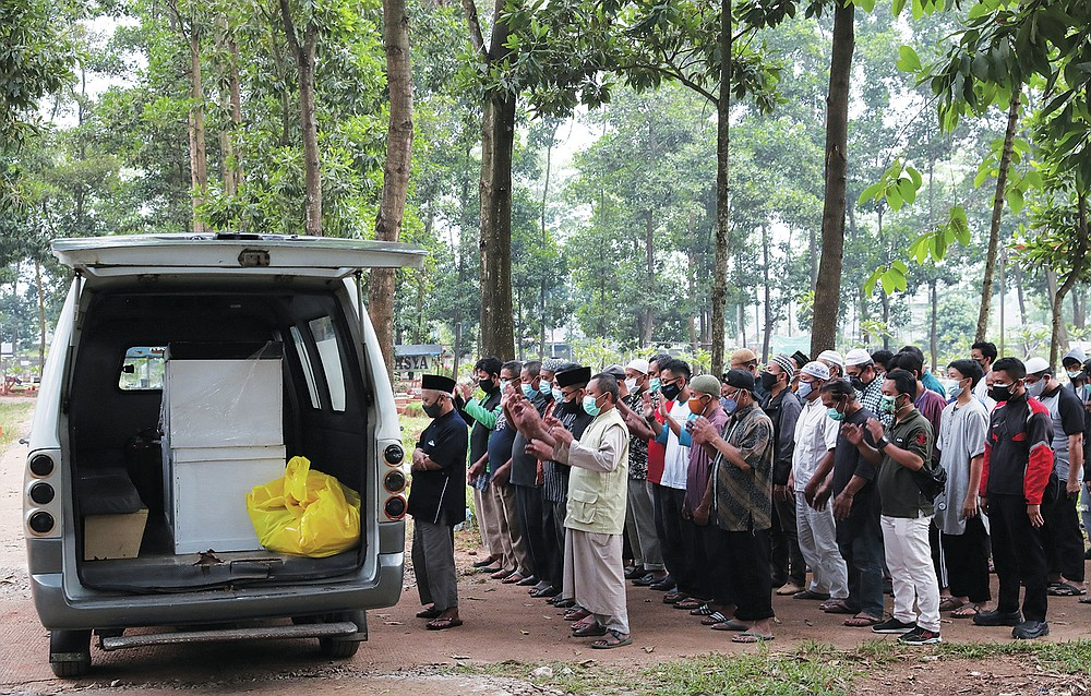 Residents pray near an ambulance carrying coffins of COVID-19 victims prior to a burial at Cipenjo cemetery in Bogor, West Java, Indonesia on July 14, 2021. With the numbers of death increasing from the latest virus surge in Indonesia which has crippled the healthcare system in Java and Bali, relatives and residents decided to volunteer to dig graves using their own hoes and shovels to help exhausting gravediggers. (AP Photo/Achmad Ibrahim)