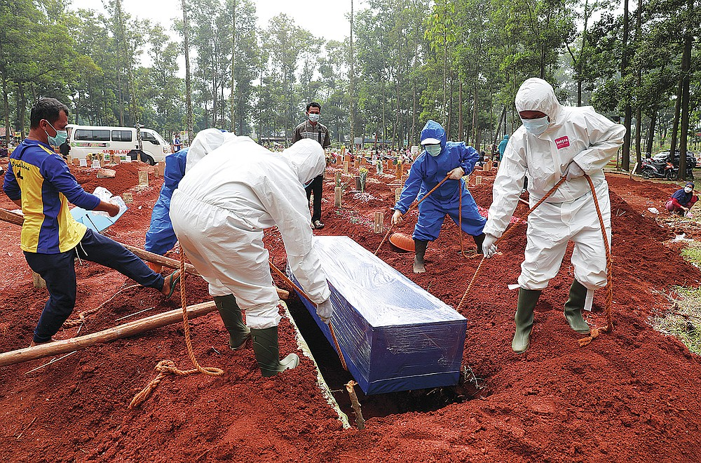 Workers in protective suits lower a coffin containing the body of a COVID-19 victim into a grave during a burial at Cipenjo cemetery in Bogor, West Java, Indonesia on July 14, 2021. With the numbers of death increasing from the latest virus surge in Indonesia which has crippled the healthcare system in Java and Bali, relatives and residents decided to volunteer to dig graves using their own hoes and shovels to help exhausting gravediggers. (AP Photo/Achmad Ibrahim)