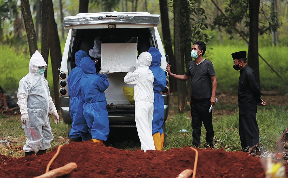 Workers in protective suits remove a coffin containing the body of a COVID-19 victim from an ambulance for burial at Cipenjo cemetery in Bogor, West Java, Indonesia on July 14, 2021. With the numbers of death increasing from the latest virus surge in Indonesia which has crippled the healthcare system in Java and Bali, relatives and residents decided to volunteer to dig graves using their own hoes and shovels to help exhausting gravediggers. (AP Photo/Achmad Ibrahim)