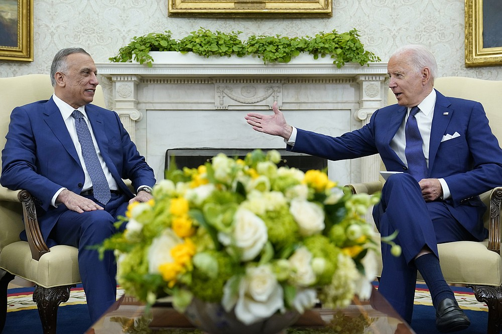 President Joe Biden, right, speaks as Iraqi Prime Minister Mustafa al-Kadhimi, left, listens during their meeting in the Oval Office of the White House in Washington, Monday, July 26, 2021. (AP Photo/Susan Walsh)