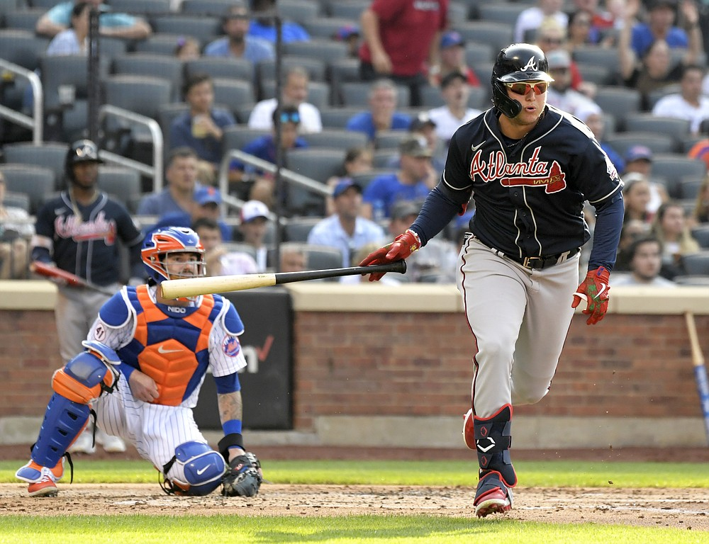 Atlanta Braves' Joc Pederson, right, hits an RBI-double scoring Guillermo Heredia as New York Mets catcher Tomas Nido, left, looks on during the third inning of the first game of a baseball doubleheader Monday, July 26, 2021, in New York. (AP Photo/Bill Kostroun)
