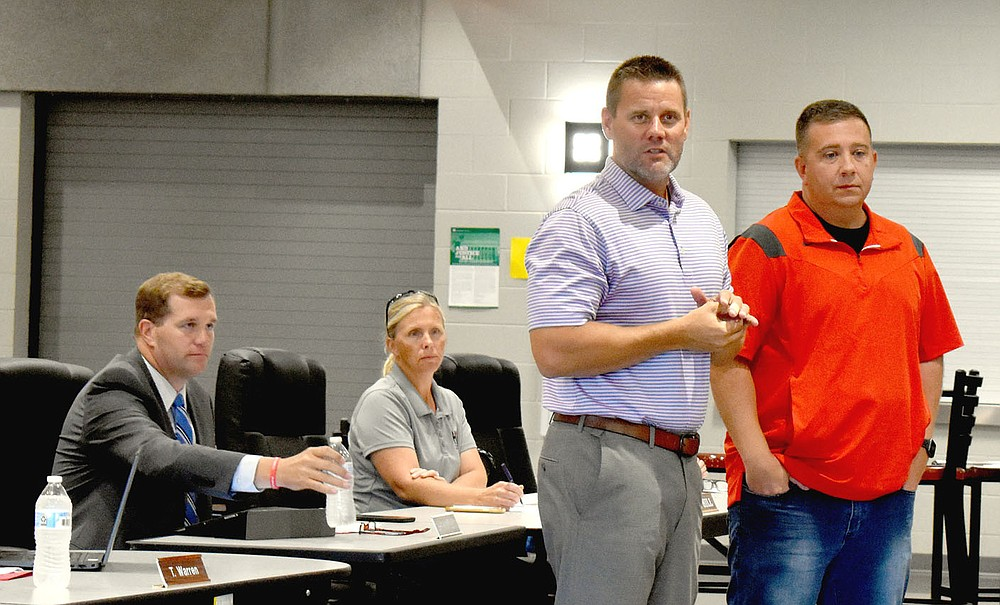 MARK HUMPHREY  ENTERPRISE-LEADER/Farmington athletic director Beau Thompson introduces girls basketball head coach Brad Johnson while superintendent Jon Paul Laffoon (left) and board vice president Amy Hill look on during a Monday, July 19 school board meeting held at the high school cafeteria. The board recognized the accomplishments of the Lady Cardinals, who finished as the Class 4A State Runner-up for the 2020-2021 season.