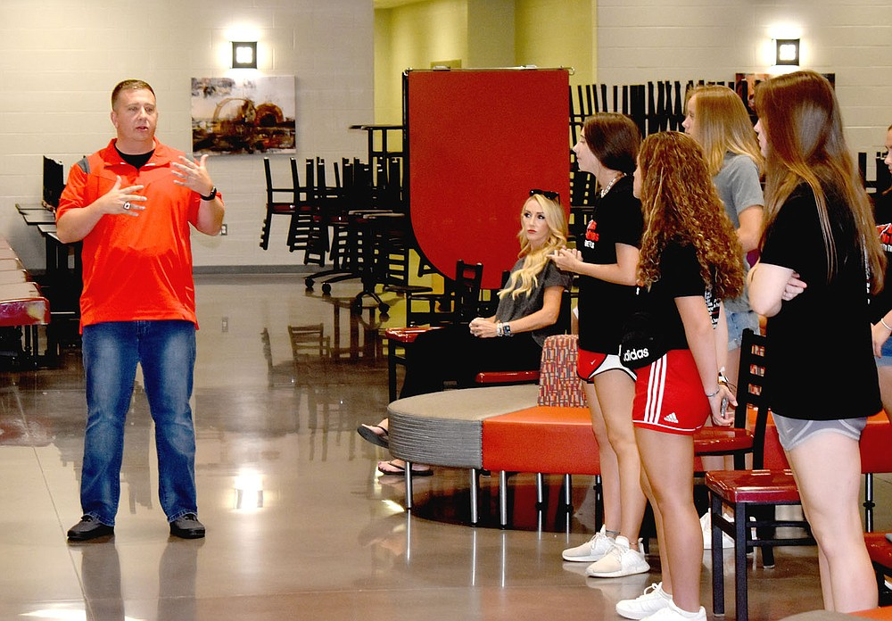 MARK HUMPHREY  ENTERPRISE-LEADER/Farmington girls basketball coach Brad Johnson recapped accomplishments for the 2020-2021 Lady Cardinal team, which graduated five players including three starters from the 2019-2020 state championship team; and fought their way back into the Class 4A State finals, which weren't played in 2020 due to covid. Farmington finished as state runner-up in 2021. The team was honored during a Monday, July 19 school board meeting. Assistant coach Jessica McCullough is seated in the background.