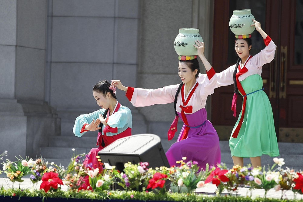 An art troupe performs in front of the Pyongyang Grand Theatre in Pyongyang, North Korea, Tuesday, July 27, 2021, to mark the Korean War armistice anniversary. The leaders of North and South Korea restored suspended communication channels between them and agreed to improve ties, both governments said Tuesday, amid a 2 ½ year-stalemate in U.S.-led diplomacy aimed at stripping North Korea of its nuclear weapons. (AP Photo/Cha Song Ho)