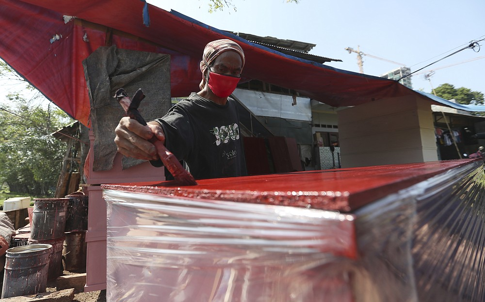 A worker paints in a process of making a coffin which will be used for victims of the coronavirus in Jakarta, Indonesia, Tuesday, July 27, 2021. Indonesia has been showing sharp increases since late June. (AP Photo/Achmad Ibrahim)