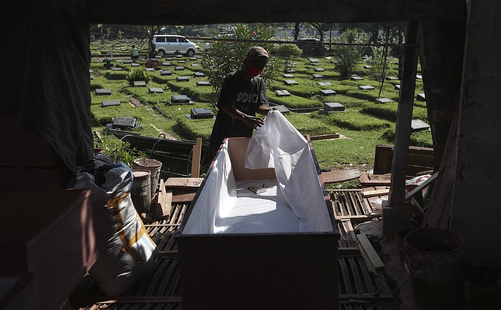 A worker makes a coffin to be used for victims of the coronavirus in Jakarta, Indonesia, Tuesday, July 27, 2021. Indonesia has been showing sharp increases since late June. (AP Photo/Achmad Ibrahim)