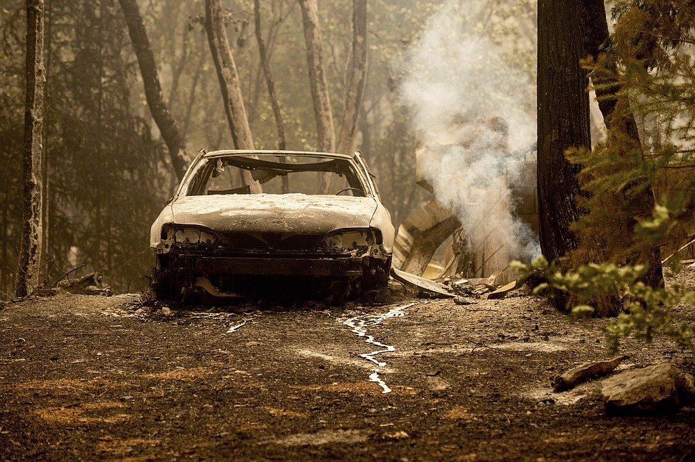 Following the Dixie Fire, a scorched vehicle rests in a driveway in the Indian Falls community of Plumas County, Calif., on Monday, July 26, 2021. (AP Photo/Noah Berger)