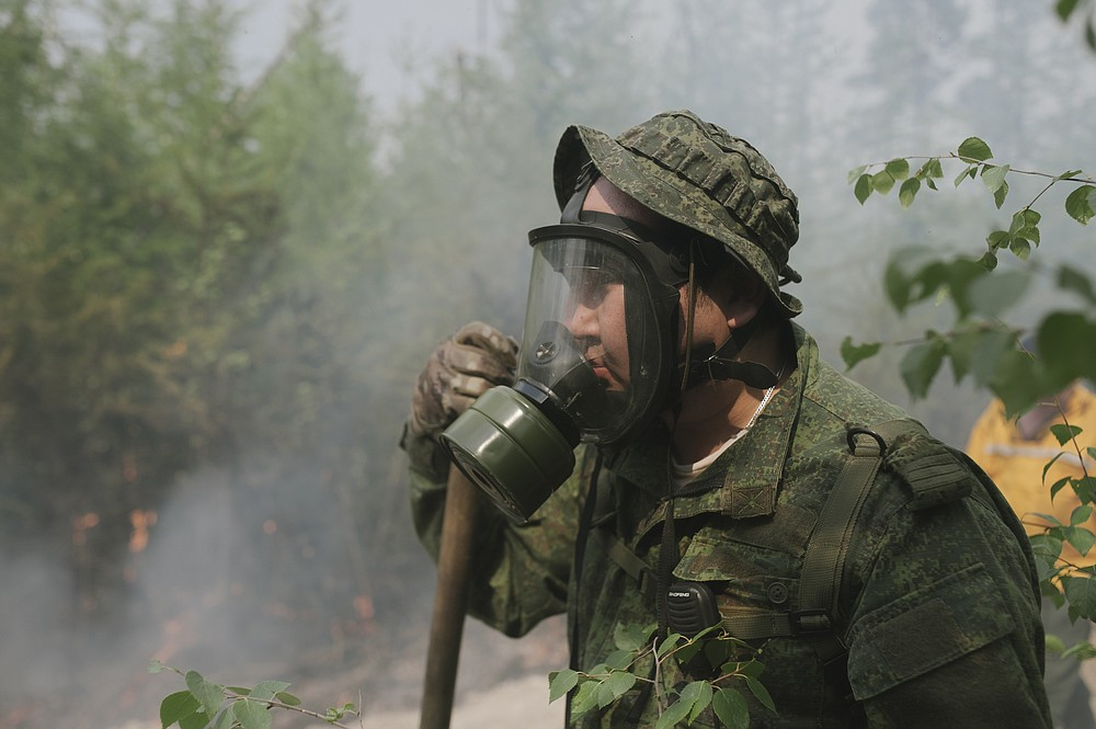 Maxim Yefremov, member of volunteers crew adjusts his gas mask as he mops up spot fires at Gorny Ulus area west of Yakutsk, Russia, Thursday, July 22, 2021. The hardest hit area is the Sakha Republic, also known as Yakutia, in the far northeast of Russia, about 5,000 kilometers (3,200 miles) from Moscow. About 85% of all of Russia's fires are in the republic, and heavy smoke forced a temporary closure of the airport in the regional capital of Yakutsk, a city of about 280,000 people. (AP Photo/Ivan Nikiforov)