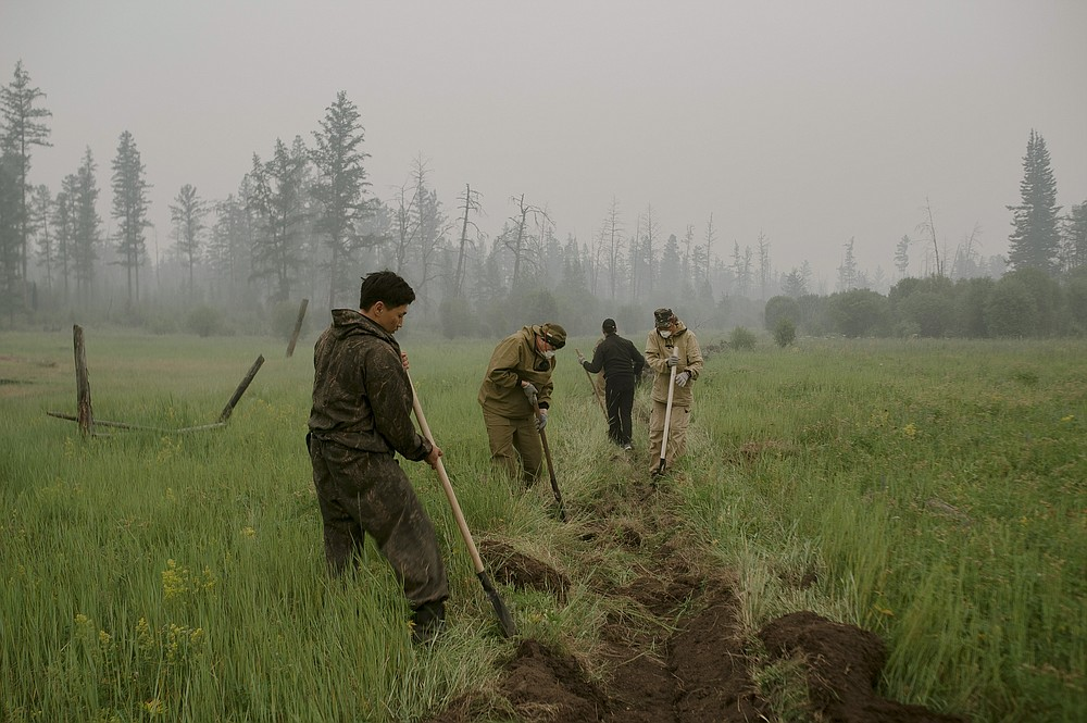 Member of volunteers crew dig a fire-break moat to stop the fire from spreading at Gorny Ulus area west of Yakutsk, Russia, Tuesday, July 20, 2021. The hardest hit area is the Sakha Republic, also known as Yakutia, in the far northeast of Russia, about 5,000 kilometers (3,200 miles) from Moscow. About 85% of all of Russia's fires are in the republic, and heavy smoke forced a temporary closure of the airport in the regional capital of Yakutsk, a city of about 280,000 people. (AP Photo/Ivan Nikiforov)