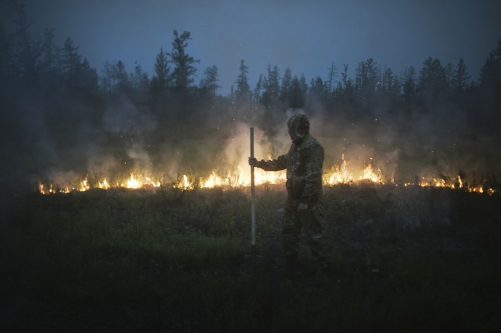 A member of volunteers crew walks past a burning grass near the edge of the fire at Gorny Ulus area west of Yakutsk, Russia, Thursday, July 22, 2021.  The hardest hit area is the Sakha Republic, also known as Yakutia, in the far northeast of Russia, about 5,000 kilometers (3,200 miles) from Moscow. About 85% of all of Russia's fires are in the republic, and heavy smoke forced a temporary closure of the airport in the regional capital of Yakutsk, a city of about 280,000 people. (AP Photo/Ivan Nikiforov)