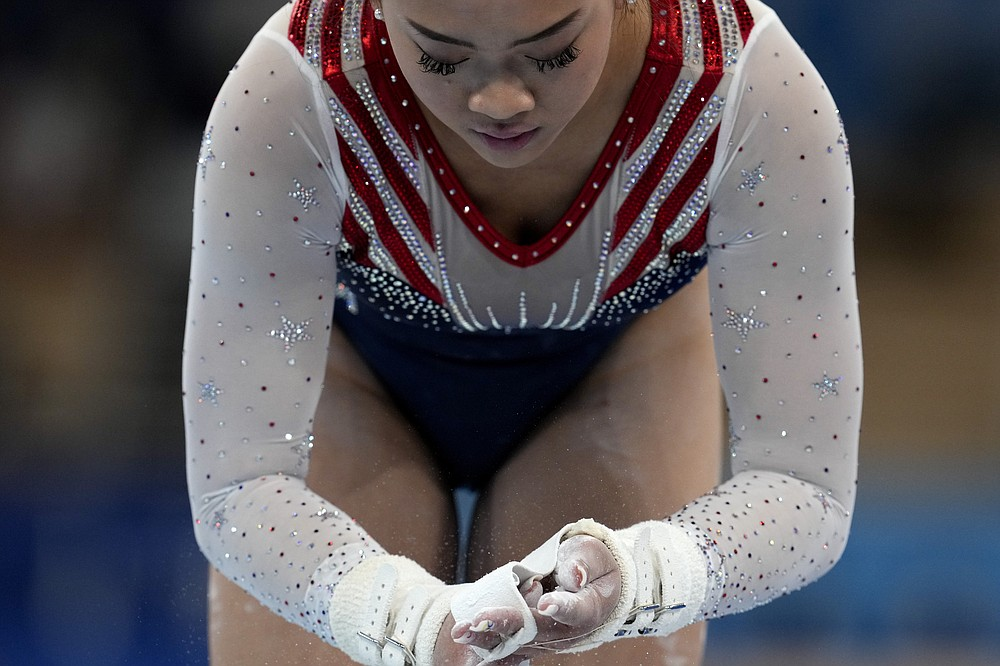 Sunisa Lee, of the United States, powders her hands before her performance on the uneven bars during the artistic gymnastics women's all-around final at the 2020 Summer Olympics, Thursday, July 29, 2021, in Tokyo. (AP Photo/Natacha Pisarenko)