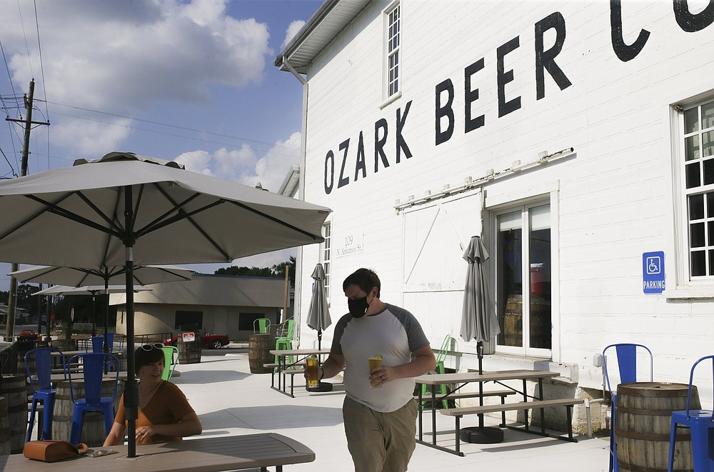 Elliot Holder of Pea Ridge (center) joins his wife Cassie Holder as he carries drinks, Friday, July 23, 2021 at Ozark Beer Company in Rogers. They expanded their patio area and added to their capacity. The brewery is in downtown Rogers and was the second largest beer producer in the state in 2019. Check out nwaonline.com/210724Daily/ for today's photo gallery.  (NWA Democrat-Gazette/Charlie Kaijo)