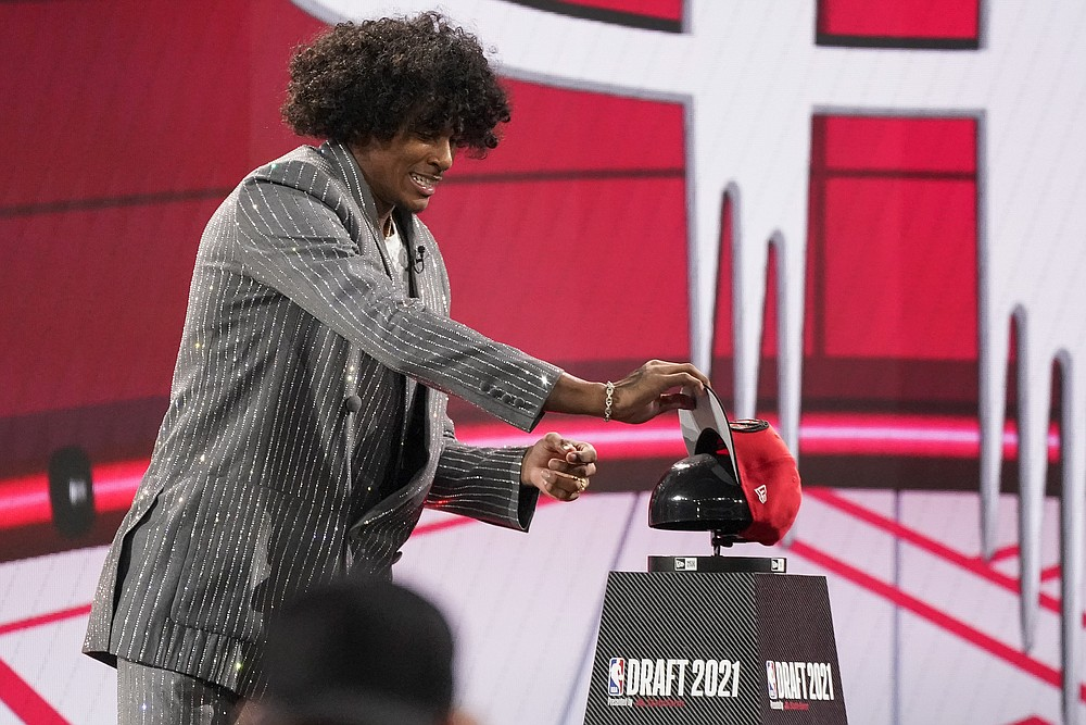 Jalen Green picks up a Houston Rockets cap after he was selected by the Houston Rockets as the second overall pick during the first round of the NBA basketball draft, Thursday, July 29, 2021, in New York. (AP Photo/Corey Sipkin)