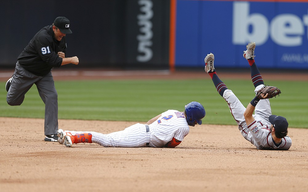 Umpire Brian Knight (91) calls New York Mets first baseman Dominic Smith (2) out at second base after the tag by Atlanta Braves shortstop Dansby Swanson (7) during the inning of a baseball game Thursday, July 29, 2021, in New York. (AP Photo/Noah K. Murray)