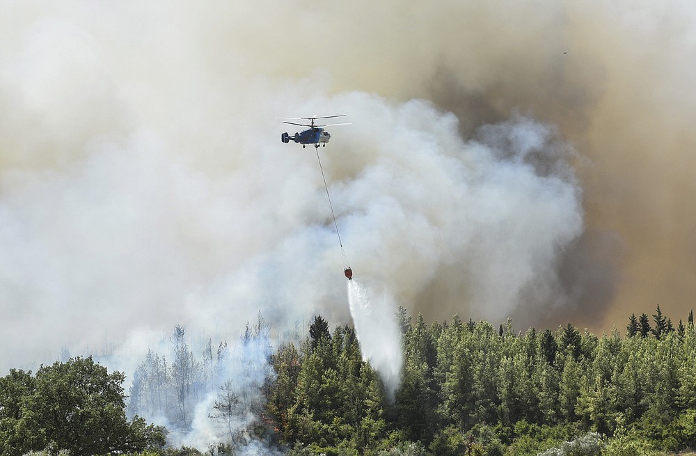 A helicopter pours star on wildfires in Kacarlar village near the Mediterranean coastal town of Manavgat, Antalya, Turkey, Saturday, July 31, 2021. The death toll from wildfires raging in Turkey's Mediterranean towns rose to six Saturday after two forest workers were killed, the country's health minister said. Fires across Turkey since Wednesday burned down forests, encroaching on villages and tourist destinations and forcing people to evacuate. (AP Photo)