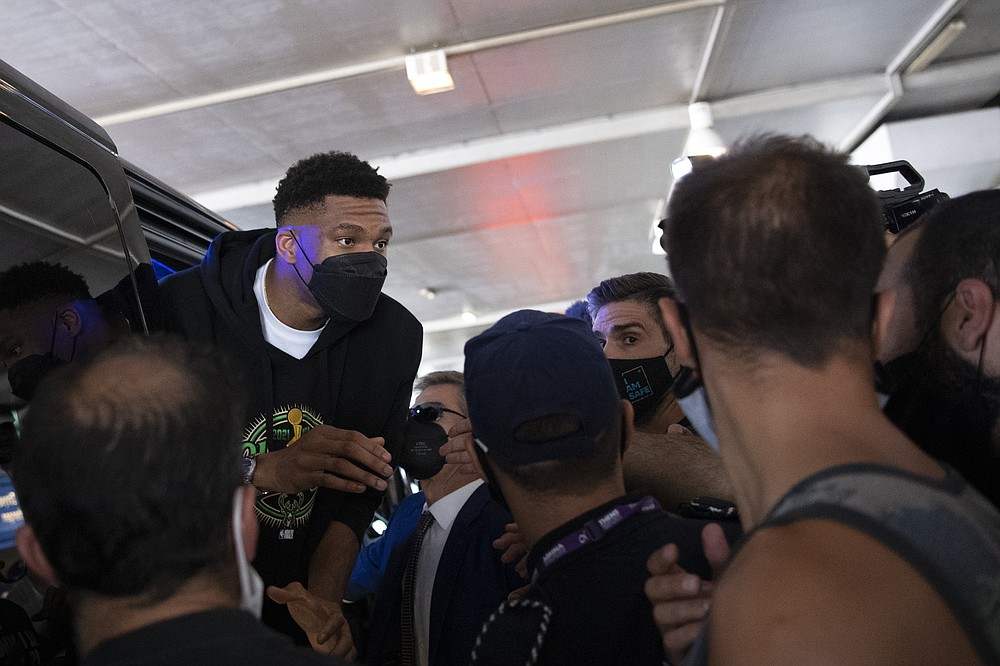 NBA Champion Giannis Antetokounmpo, of the Milwaukee Bucks, who was named NBA Finals Most Valuable Player, talks with fans as he enters a van, at the Eleftherios Venizelos International Airport, in Athens, Greece, Sunday, Aug. 1, 2021. The NBA champion and finals MVP plans to stay in Greece for a few days, before returning to the U.S., where his girlfriend expects their second child later this month. (AP Photo/Michael Varaklas)