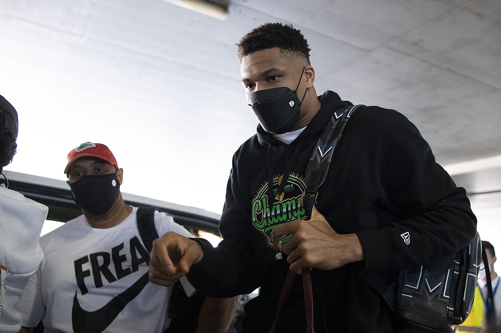 NBA Champion Giannis Antetokounmpo, of the Milwaukee Bucks, who was named NBA Finals Most Valuable Player, arrives at the Eleftherios Venizelos International Airport, in Athens, Greece, Sunday, Aug. 1, 2021. The NBA champion and finals MVP plans to stay in Greece for a few days, before returning to the U.S., where his girlfriend expects their second child later this month. (AP Photo/Michael Varaklas)