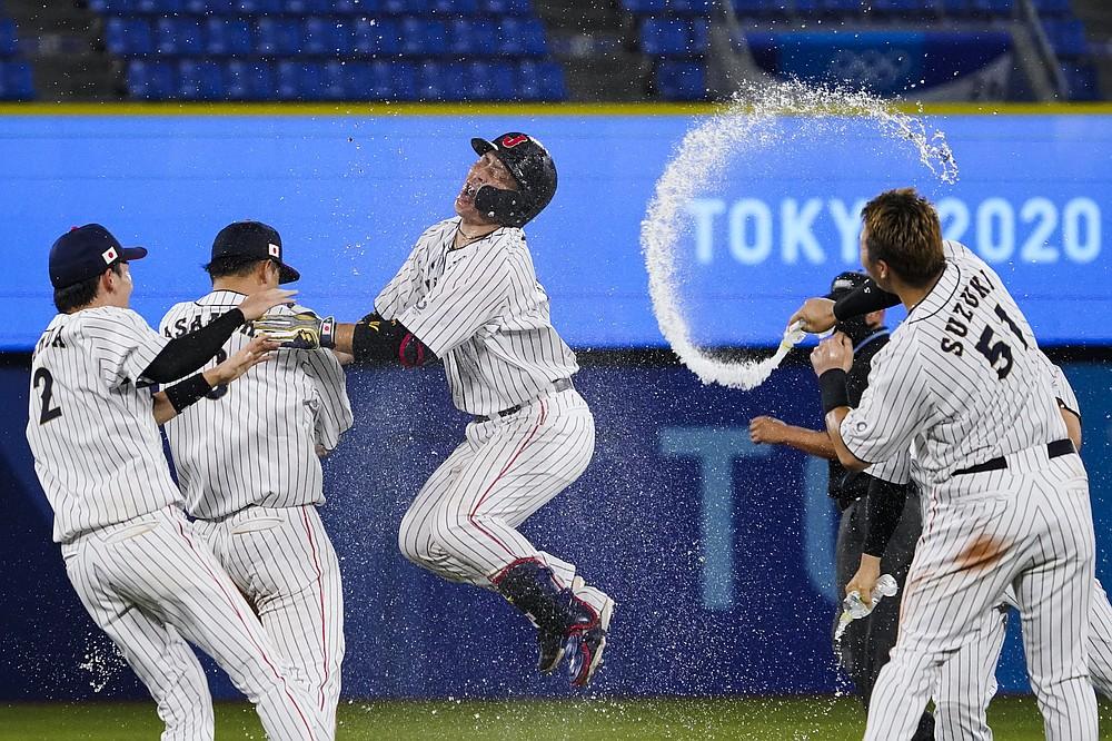 Japan's Takuya Kai, center, and teammates celebrates their wins after a baseball game against the United States at the 2020 Summer Olympics, Monday, Aug. 2, 2021, in Yokohama, Japan. Japan won 7-6. (AP Photo/Sue Ogrocki)