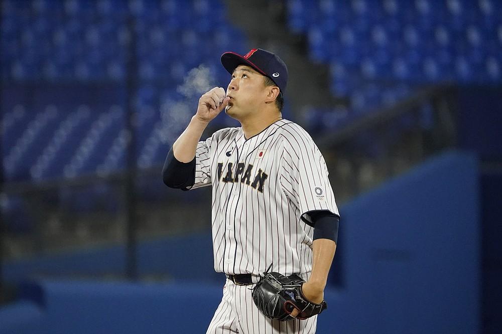 Japan's Masahiro Tanaka blows chalk off of his hand during a baseball game against the United States at the 2020 Summer Olympics, Monday, Aug. 2, 2021, in Yokohama, Japan. (AP Photo/Sue Ogrocki)