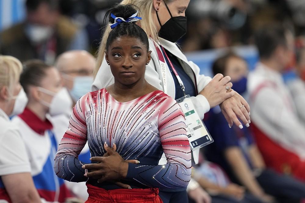 США Симона Байлз смотрит на результат после выступления на бревне во время финала женской органной гимнастики на летних Олимпийских играх 2020 года, во вторник, 3 августа 2021 года, в Токио, Япония.  (AP Photo / Наташа Писаренко)