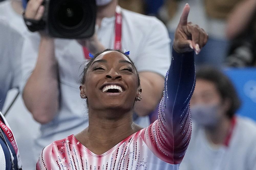 Симона Байлз из США показывает своим товарищам по команде на трибунах после выступления на бревне во время финала женской спортивной гимнастики на снарядах на летних Олимпийских играх 2020 года во вторник, 3 августа 2021 года, в Токио, Япония.  (AP Photo / Эшли Лэндис)