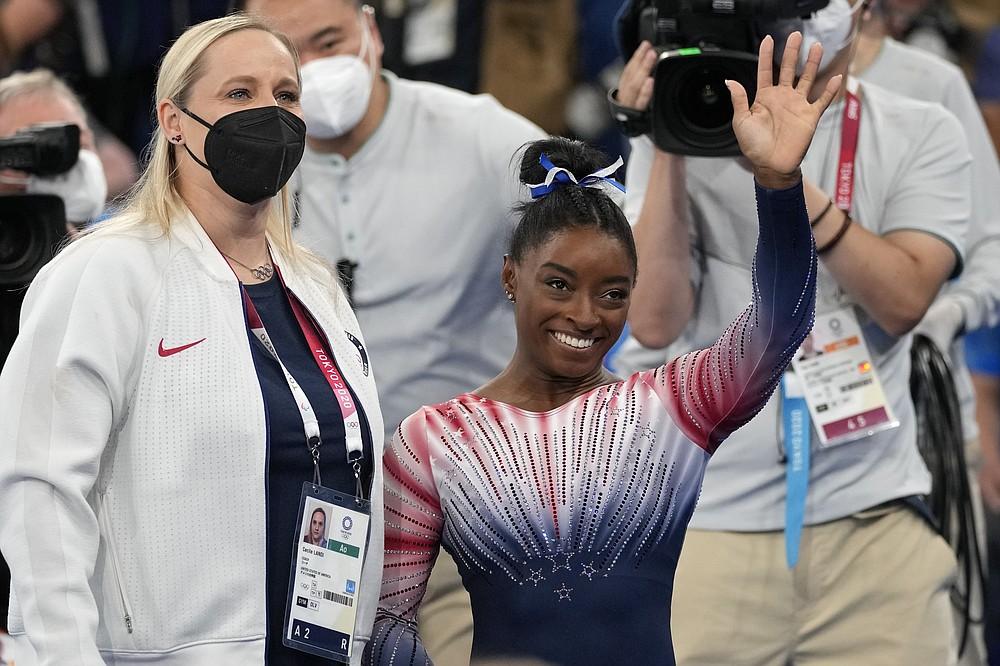Симона Байлз из США машет рукой рядом со своим тренером Сесилом Лэнди после выступления на бревне во время финала женской органной гимнастики на летних Олимпийских играх 2020 года, вторник, 3 августа 2021 года, в Токио, Япония.  (AP Photo / Эшли Лэндис)