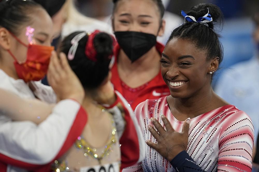Симона Байлс из США улыбается, когда китаец Тан Сицзин (слева) обнимает своего товарища по команде Гуань Шэньчжэня после того, как последний выиграл золотую медаль на бревне во время финала женской спортивной гимнастики на летних Олимпийских играх 2020 года во вторник, 3 августа.  3 января 2021 года в Токио, Япония.  Байлз выиграл бронзовую медаль.  (AP Photo / Наташа Писаренко)