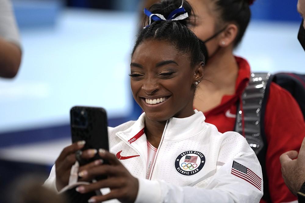 Американка Симона Байлз разговаривает по телефону после бега на бревне во время финала женской органной гимнастики на летних Олимпийских играх 2020 года, вторник, 3 августа 2021 года, в Токио, Япония.  (AP Photo / Эшли Лэндис)