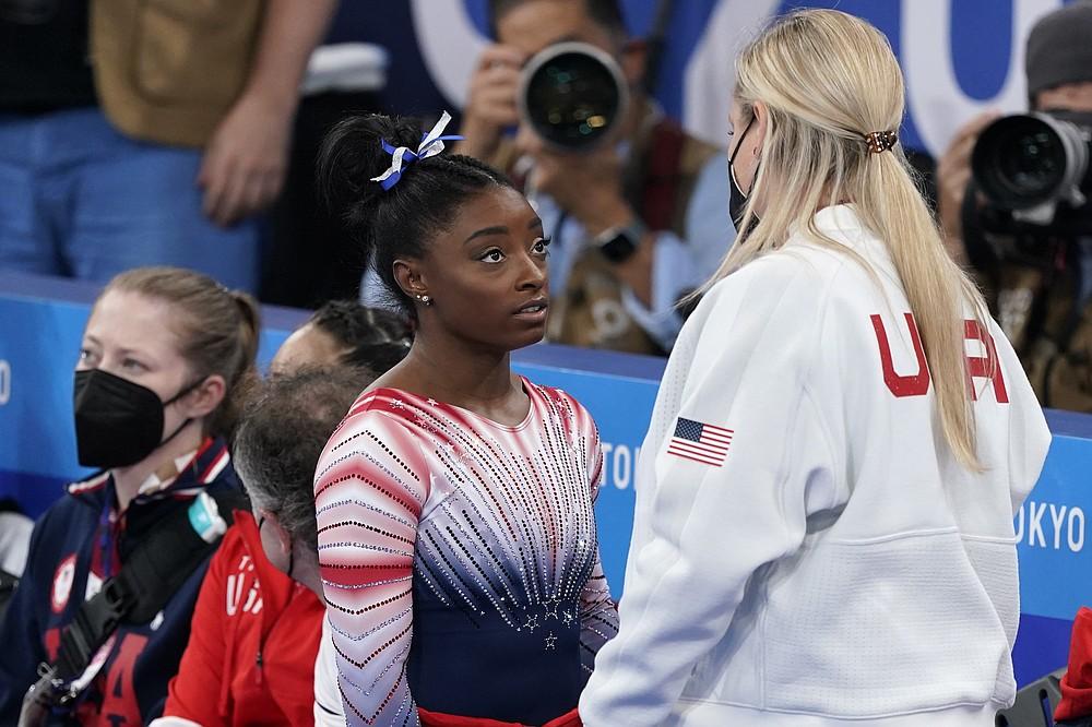 Американка Симона Байлз разговаривает с тренером Сесилом Лэнди после выступления на бревне во время финала женских соревнований по технической гимнастике на летних Олимпийских играх 2020 года во вторник, 3 августа 2021 года, в Токио, Япония.  (AP Photo / Jae C. Hong)