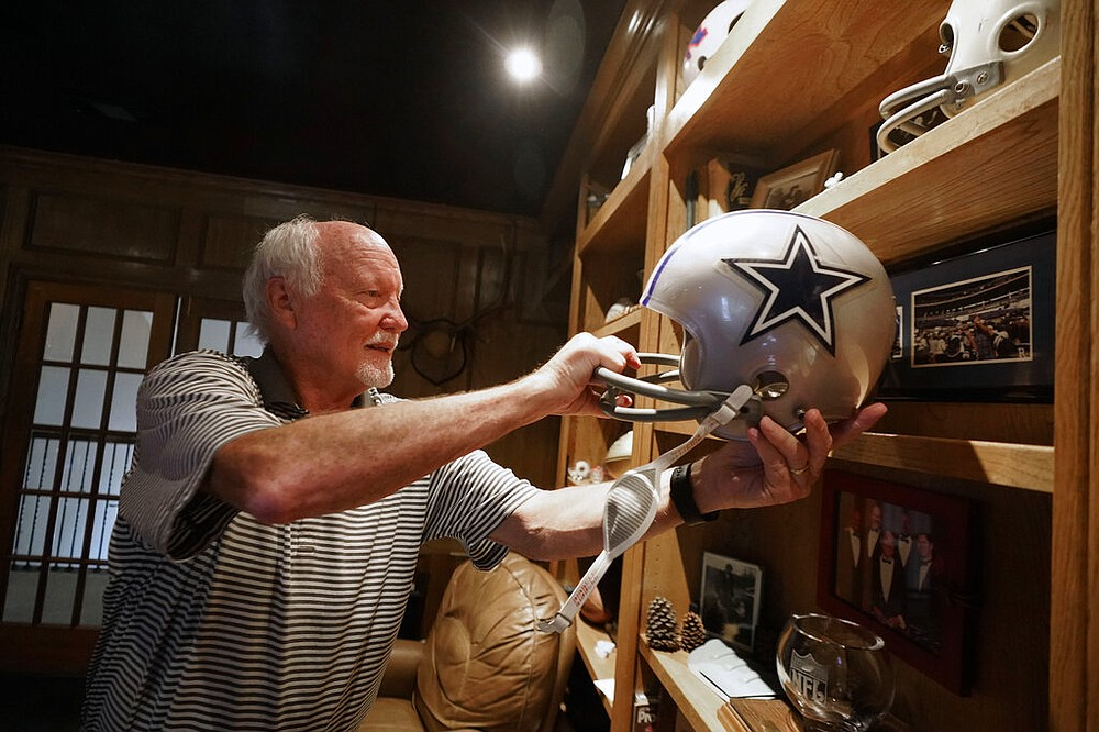 Former Dallas Cowboys and NFL football great Cliff Harris pulls out the helmet he wore during his playing days during an interview at his home in North Dallas, Wednesday, June 30, 2021. (AP Photo/LM Otero)