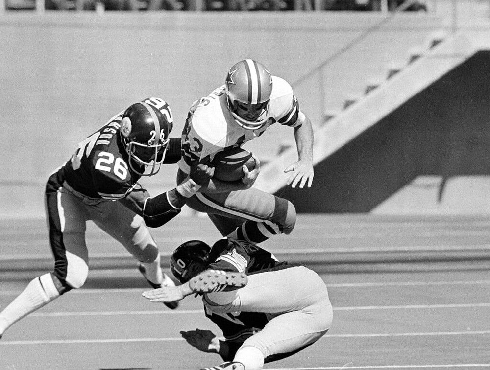 File-This Oct. 8, 1972, file photo shows Dallas Cowboys safety Cliff Harris (43) making a 45-yard return on a second quarter punt Oct. 8, 1972 in Irving, Texas, before being brought down by Steelers' Preston Pearson (26) and Roy Gerela (10). (AP Photo/File)