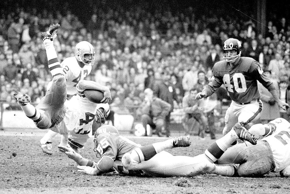 FILE - In this Dec. 12, 1971, file photo, Dallas Cowboys' Cliff Harris (43) is upended by New York Giants' Ralph Heck (55) during a punt return in he second quarter of an NFL football game in New York. (AP Photo/Ray Stubblebine, File)