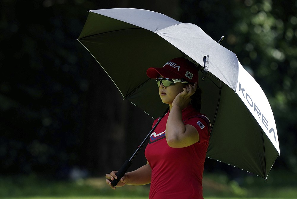 Hyojoo Kim, of South Korea, stands under an umbrella on the 16th hole during the first round of the women's golf event at the 2020 Summer Olympics, Wednesday, Aug. 4, 2021, at the Kasumigaseki Country Club in Kawagoe, Japan. (AP Photo/Matt York)