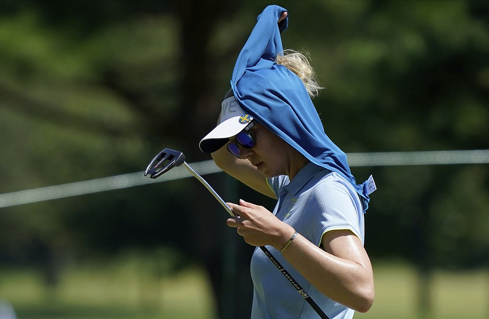 Madelene Sagstrom, of Sweden, covers her head with a towel during the first round of the women's golf event at the 2020 Summer Olympics, Wednesday, Aug. 4, 2021, at the Kasumigaseki Country Club in Kawagoe, Japan. (AP Photo/Matt York)