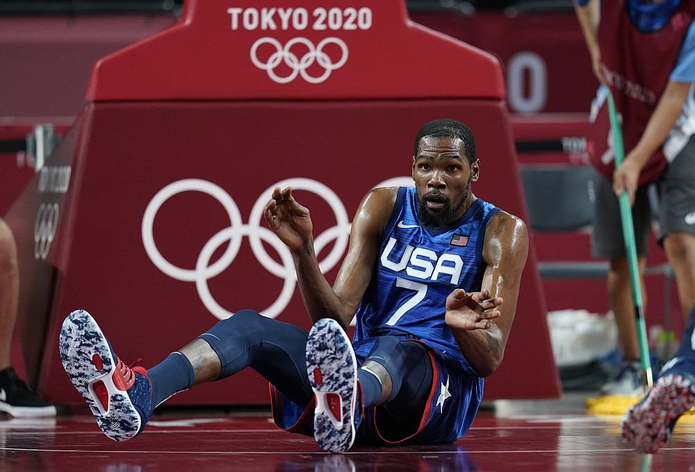 United States' Kevin Durant (7) reacts after falling on the court in an attempt to take control of the ball during men's basketball quarterfinal game against Spain at the 2020 Summer Olympics, Tuesday, Aug. 3, 2021, in Saitama, Japan. (AP Photo/Charlie Neibergall)