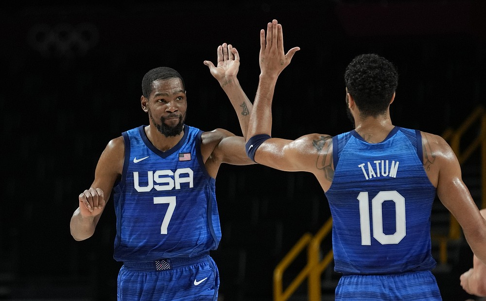 United States' Kevin Durant (7), left, and teammate Jayson Tatum (10) celebrate their win in the men's basketball quarterfinal game against Spain at the 2020 Summer Olympics, Tuesday, Aug. 3, 2021, in Saitama, Japan. (AP Photo/Eric Gay)