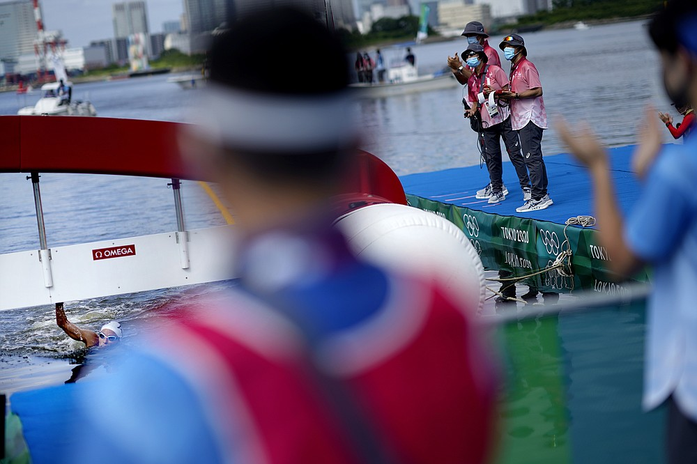 Officials applaud as Souad Nefissa Cherouati, of Algeria, finishes last in the women's marathon swimming event at the 2020 Summer Olympics, Wednesday, Aug. 4, 2021, in Tokyo. (AP Photo/David Goldman)