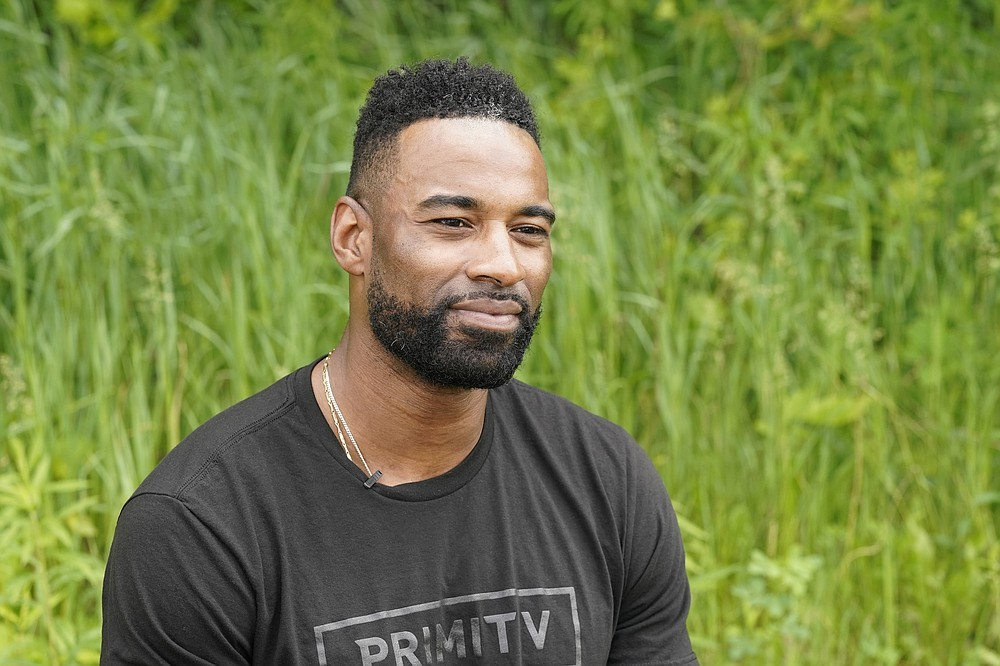 """Calvin Johnson is interviewed in Webberville, Mich. , Friday, June 4, 2021. Calvin Johnson is simply in awe that he will soon join Jim Brown and Gale Sayers as Pro Football Hall of Famers inducted at the age of 35 years old or younger. """"That's football royalty, man,"""" Johnson said in an interview with The Associated Press. """"When you hear those guys' names, you're just like, 'Wow.'""""(AP Photo/Carlos Osorio)"""