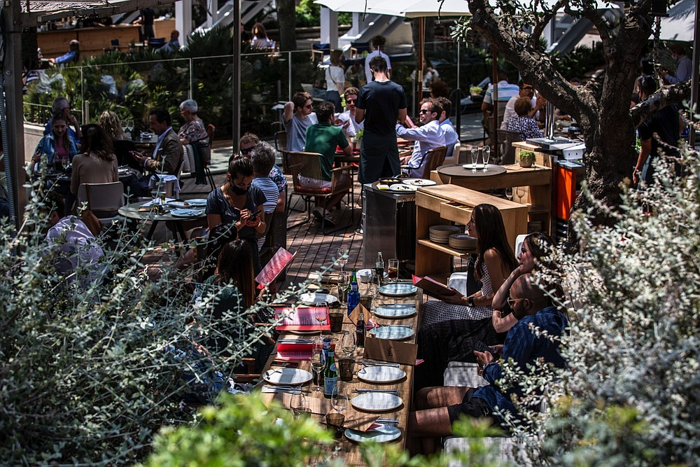 Customers dine on a restaurant terrace on Barceloneta promenade in Barcelona, Spain, in June. (Bloomberg/Angel Garcia)