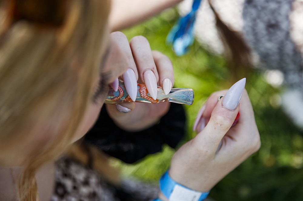 A festivalgoer smokes cannabis near the T-Mobile stage while Orville Peck performs during the first day of Lollapalooza in Chicago's Grant Park on July 29, 2021.  Illinois dispensaries sold a record $127.8 million in recreational marijuana in July, with a big boost coming from out-of-state fans who converged on Chicago for the Lollapalooza music festival (Armando L. Sanchez/Chicago Tribune via AP)