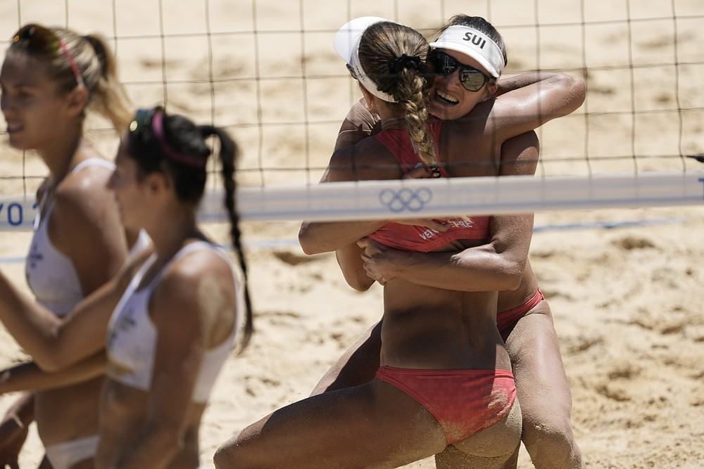 Anūks Vergs Debre, otrais no labās puses, Šveice, apskauj komandas biedri Džoannu Heidrihu, svinot uzvaru pludmales volejbola sieviešu bronzas mačā pret Latviju 2020. gada vasaras olimpiskajās spēlēs, piektdien, 2021. gada 6. augustā, Tokijā, Japānā.  (AP foto/ Petros Giannakouris)