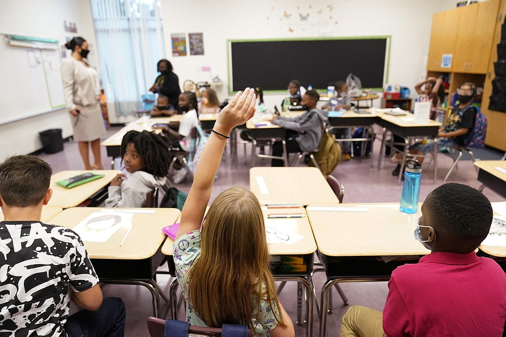 A student raises their hand in a classroom at Tussahaw Elementary school on Wednesday, Aug. 4, 2021, in McDonough, Ga.  Schools have begun reopening in the U.S. with most states leaving it up to local schools to decide whether to require masks. (AP Photo/Brynn Anderson)