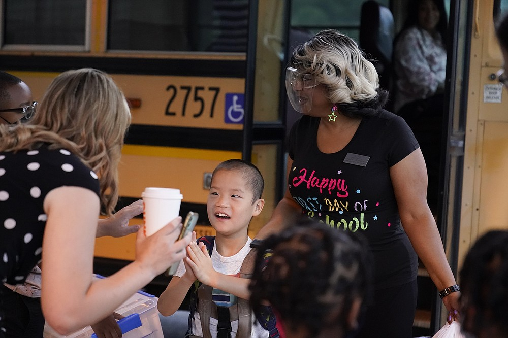Teachers greet students when the arrive to school off the school bus at Tussahaw Elementary school on Wednesday, Aug. 4, 2021, in McDonough, Ga. Schools have begun reopening in the U.S. with most states leaving it up to local schools to decide whether to require masks.   (AP Photo/Brynn Anderson)