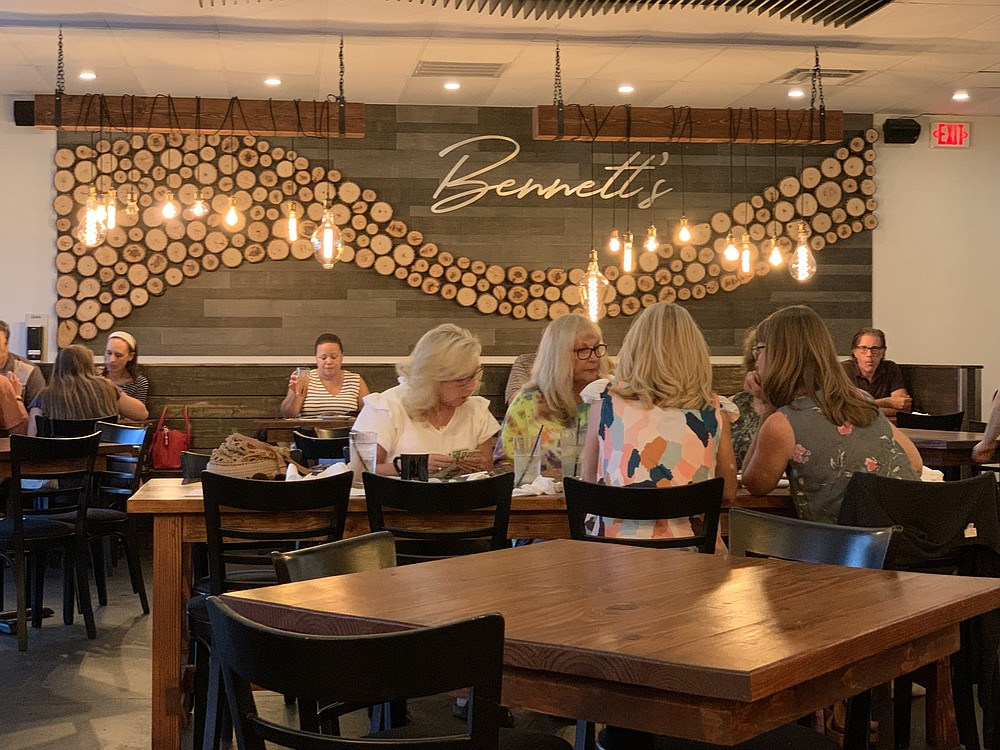 Bennett's decor includes a log-themed feature wall and, over some tables, a whimsical assortment of hanging light bulbs. (Arkansas Democrat-Gazette/Eric E. Harrison)